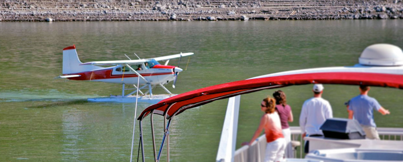 People on deck of houseboat with small seaplane in the background | Events | Lake Roosevelt Adventures